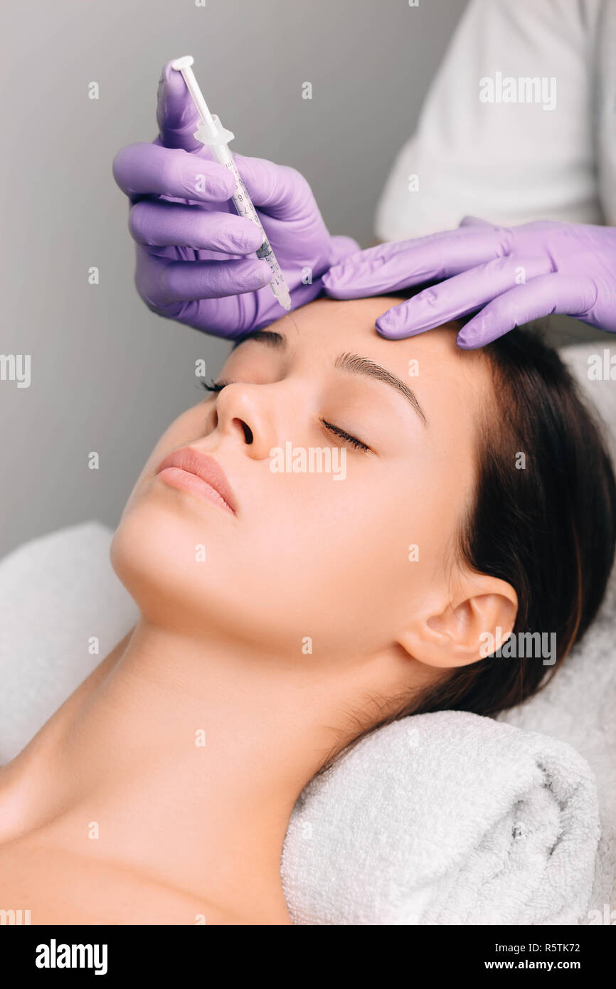 woman having facial injections for facelift and anti-aging effect, wrinkle forehead Stock Photo