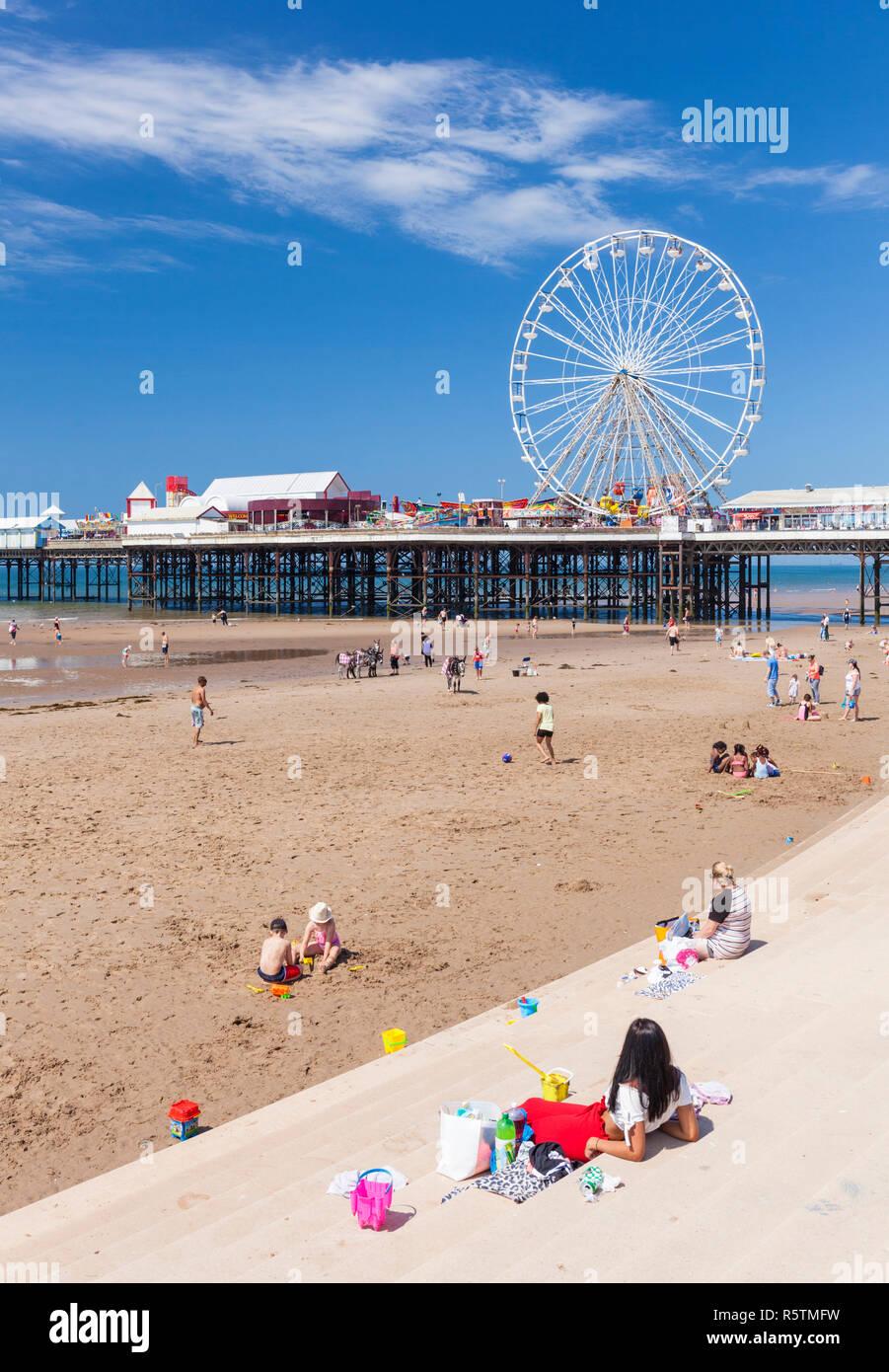 Blackpool beach summer ferris wheel on Blackpool central pier Blackpool Lots of people on the sandy beach at Blackpool Lancashire England UK GB Europe - Stock Image