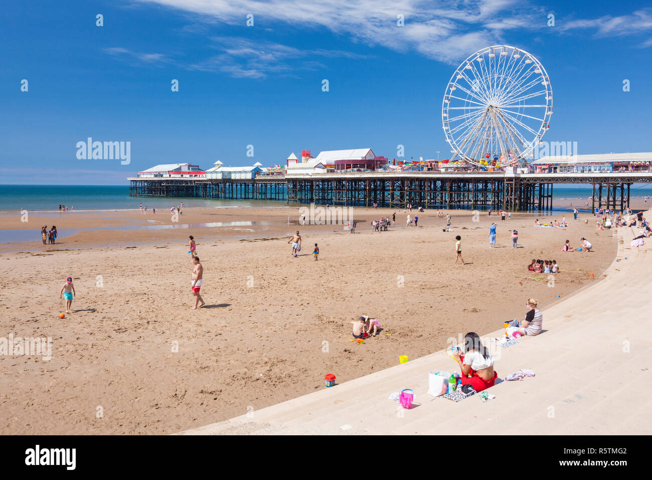 Blackpool beach summer ferris wheel on Blackpool central pier Blackpool with people on the sandy beach at Blackpool Lancashire England UK GB Europe - Stock Image