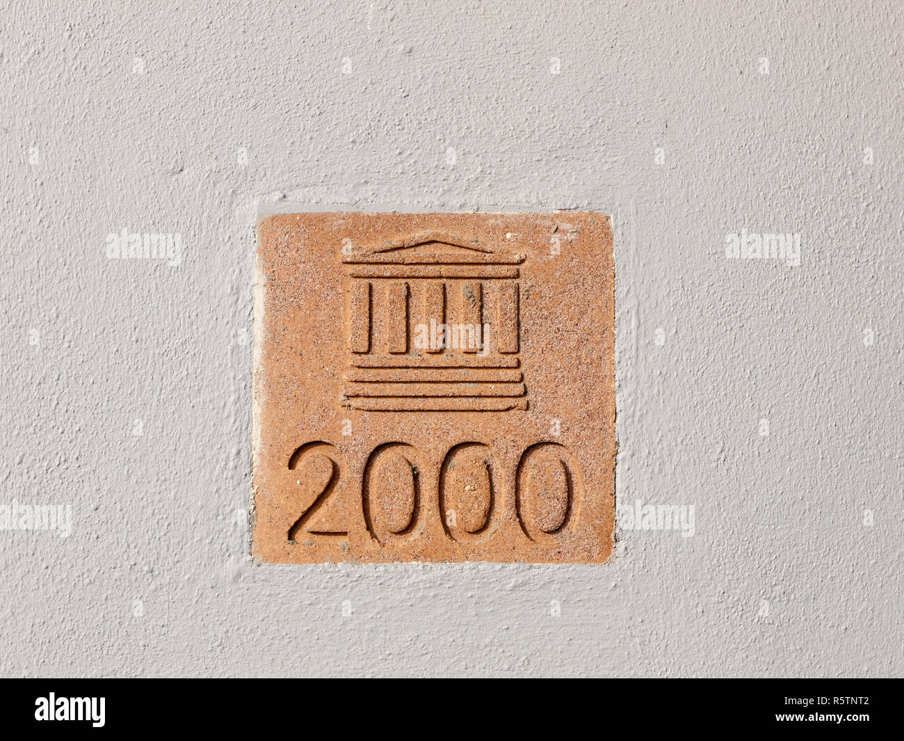 sign on wall outside 2000 column building plaque Stock Photo