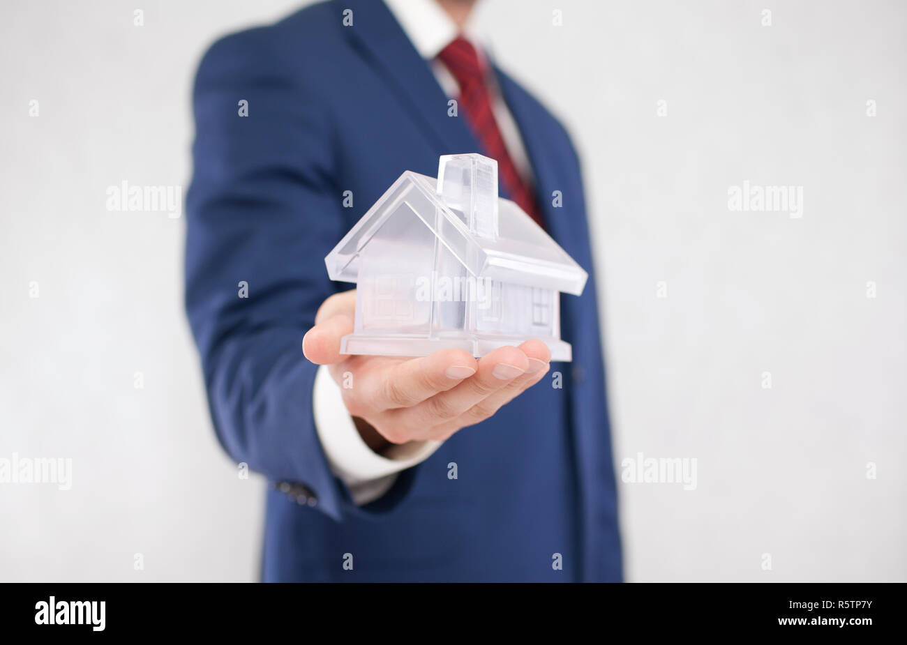 Businessman with crystal house in hand - Stock Image