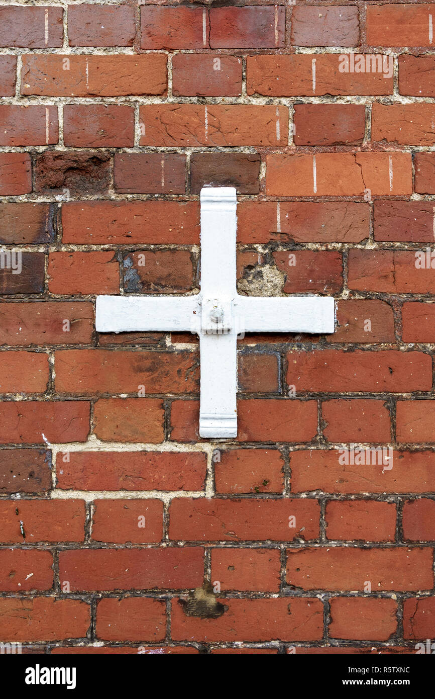 White painted metal wall tie on red brick wall - Stock Image