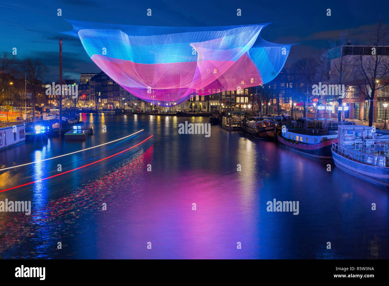 Amsterdam illuminated in winter time during Amsterdam Light Festival with light trails of passing round trip boat. Stock Photo