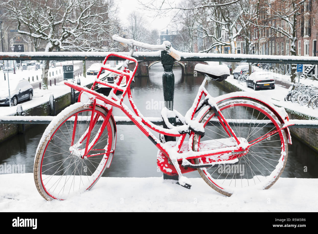 Red bike on a bridge in Amsterdam with snow. Stock Photo