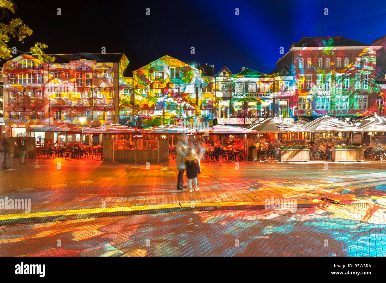 """Square with terrace and colorful light projection, artwork """"Immersive decelerator"""" (Georg Reisch of Pani) during light art festival GLOW Eindhoven. Stock Photo"""