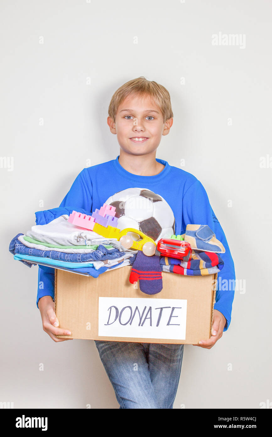 Donation concept. Kid holding donate box with clothes, books and toys - Stock Image