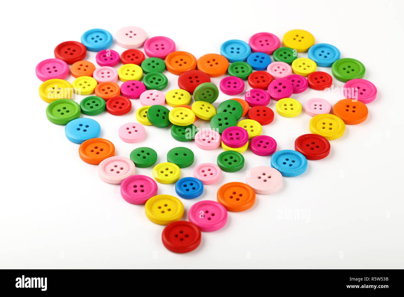 Heart shaped of colorful sewing buttons on white Stock Photo