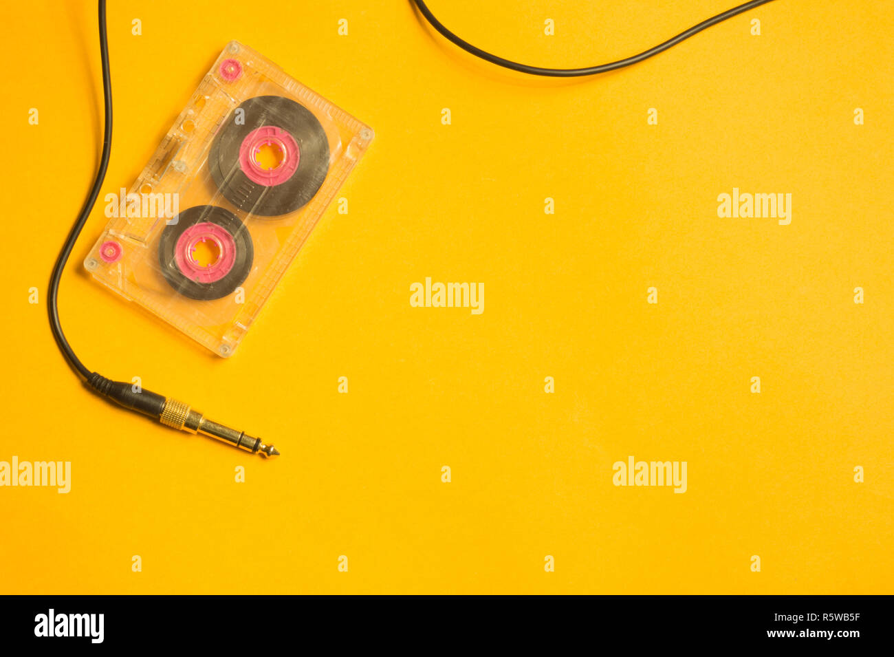 Retro cassette tape and audio jack on the yellow background Stock Photo