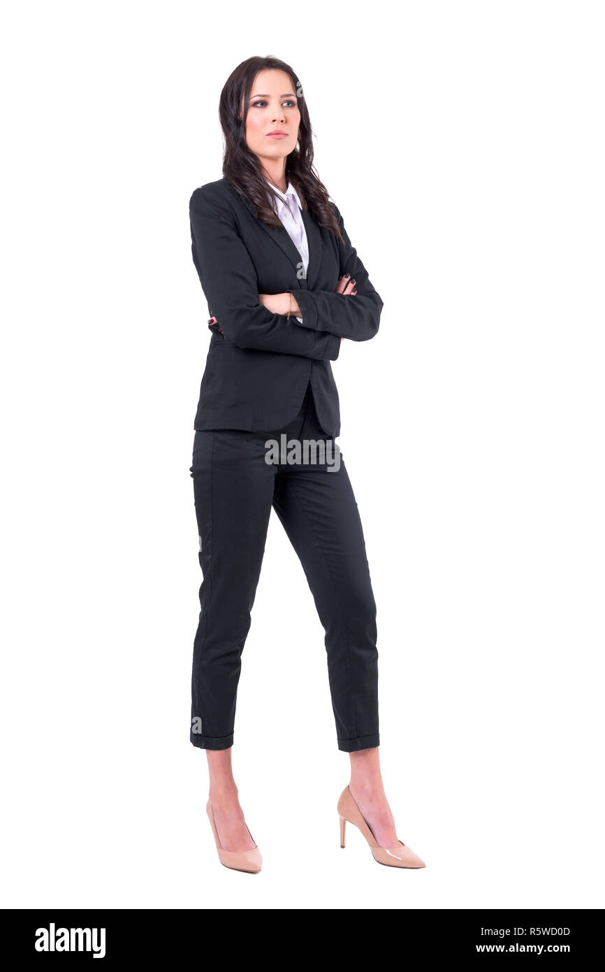 Serious skeptical business woman with crossed arms in elegant black suits looking away. Full body isolated on white background. - Stock Image