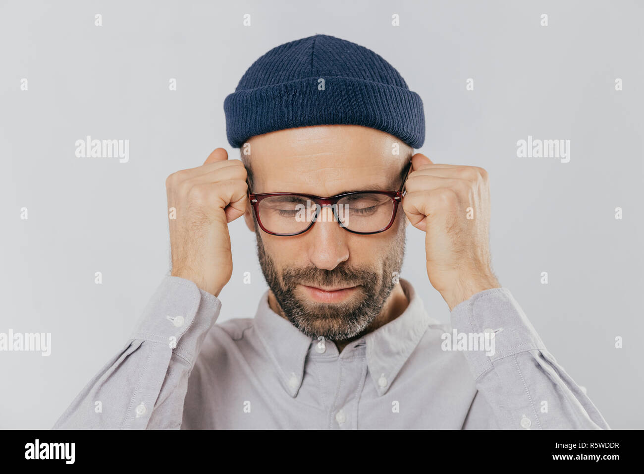 Close up shot of stressful unshaven man keeps hand near temples, has terrible headache, suffers from pain, wears headgear, spectacles, isolated over w - Stock Image