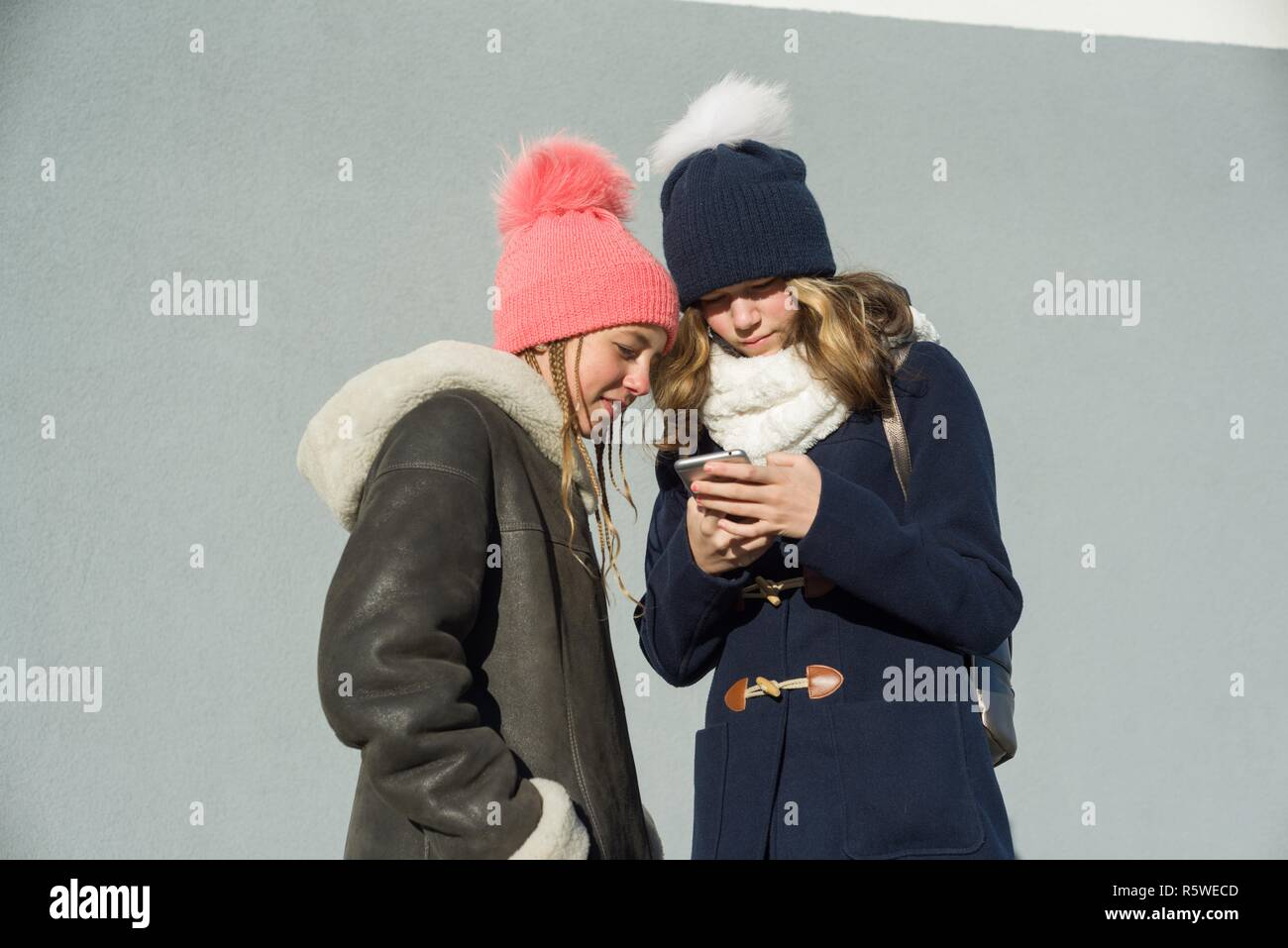 Close-up outdoor winter portrait of two teenage girls students in profile smiling and talking, girls looking at mobile phone. - Stock Image