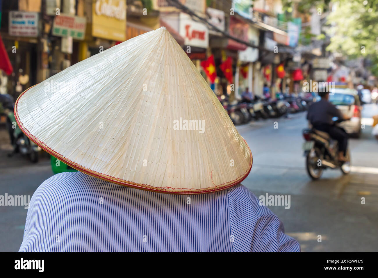 unrecognizable female in traditinal asian hat on the street of Hanoi, Vietnam - Stock Image