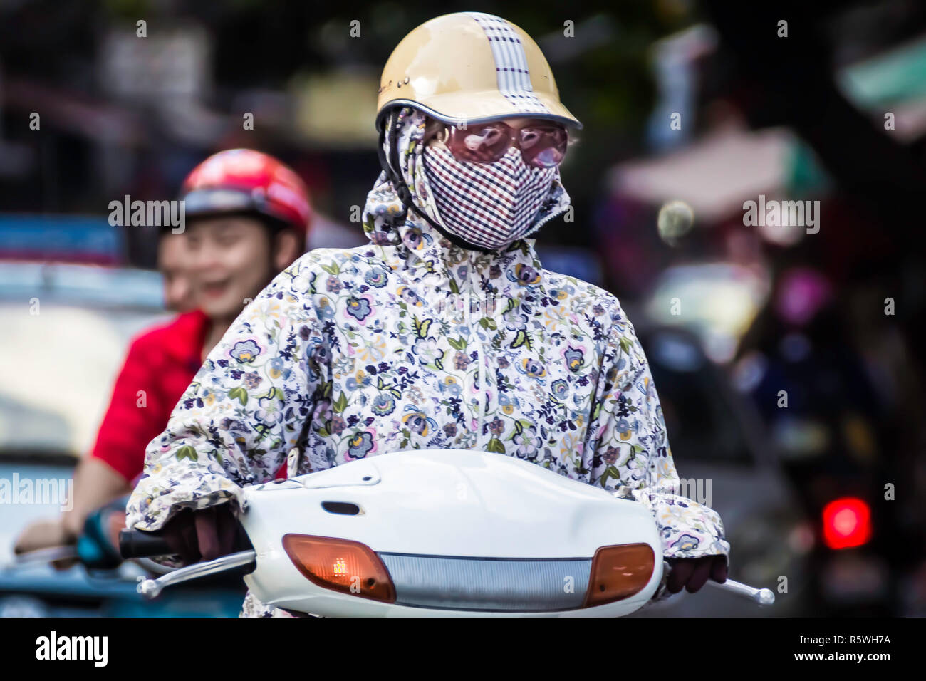female in protective against air pollution mask and helmet. Car reflection in sunglasses. - Stock Image