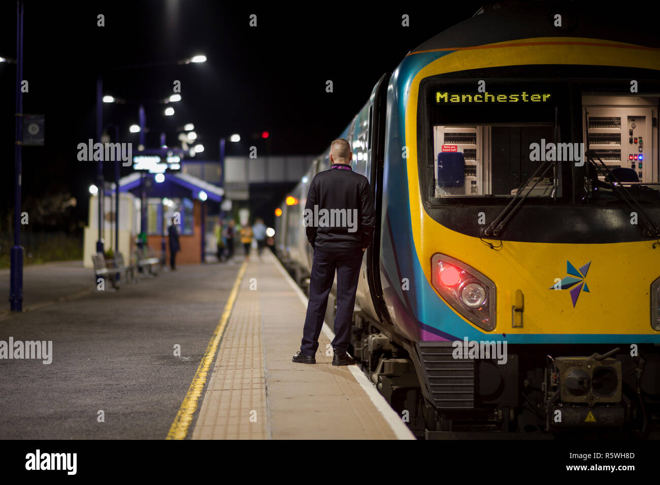 The guard / conductor of a First Transpennine express train carrying out safety checks before dispatching his his train at Brough. - Stock Image