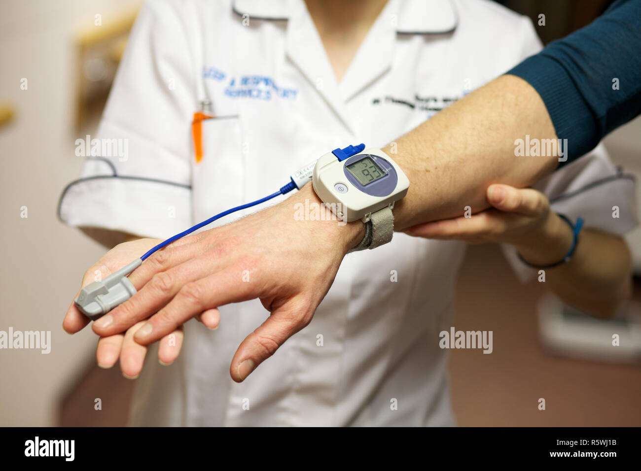 A nurse uses a pulse oximeter to monitor a patients oxygen saturation - Stock Image