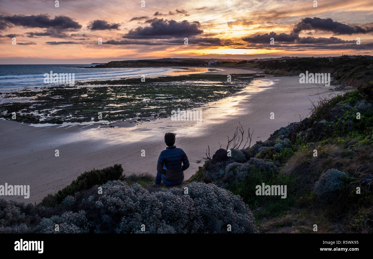 A woman in her late 20s watches the sunset at Back Beach, Torquay in Australia - Stock Image