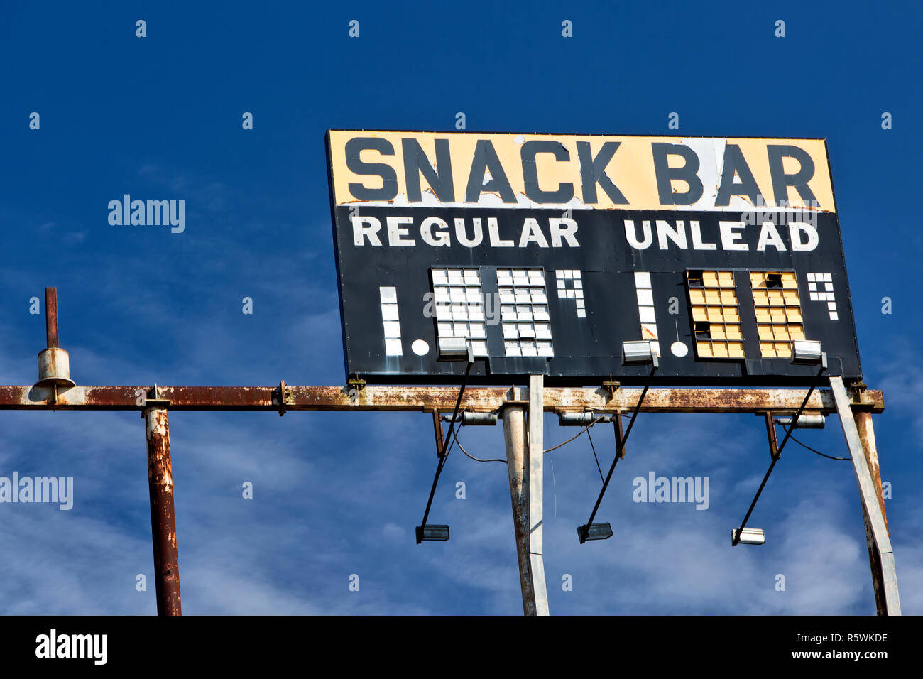 Elevated Vintage Gas Station Sign 'Snack Bar - Regular - Unlead' gasoline, against a scattered blue sky. - Stock Image