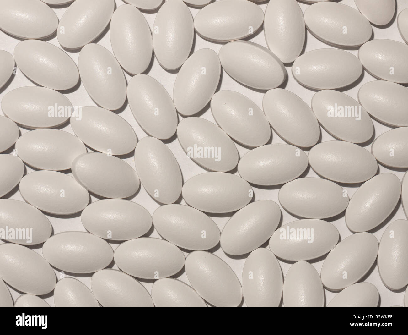 many white generic tablet pills on a white background - Stock Image