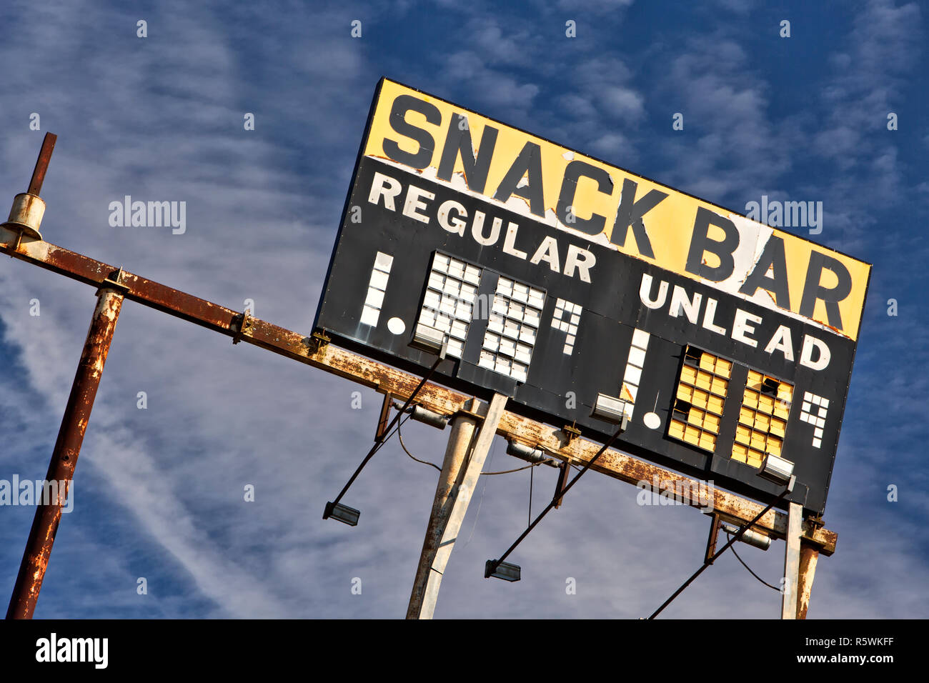 Elevated Vintage Gas Station Sign 'Snack Bar - Regular & Unlead'  gasoline,  against a scattered blue sky. - Stock Image