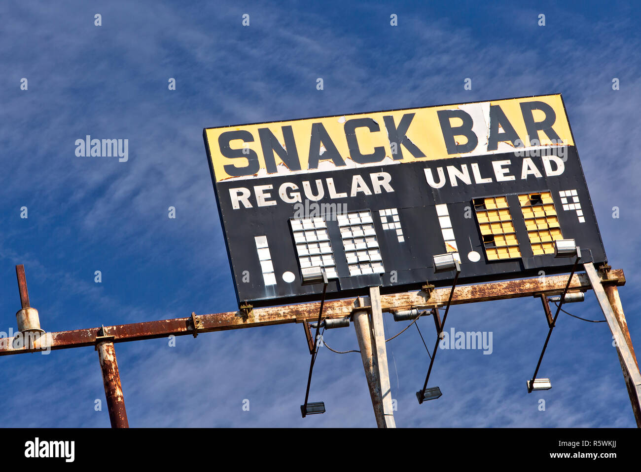 Elevated Vintage Gas Station Sign 'Snack Bar - Regular - Unlead' gasoline,  rusty metal frame, against a scattered blue sky. - Stock Image