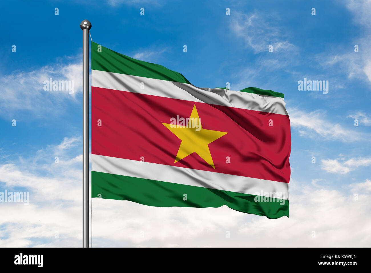Flag of Suriname waving in the wind against white cloudy blue sky. Surinamese flag. - Stock Image