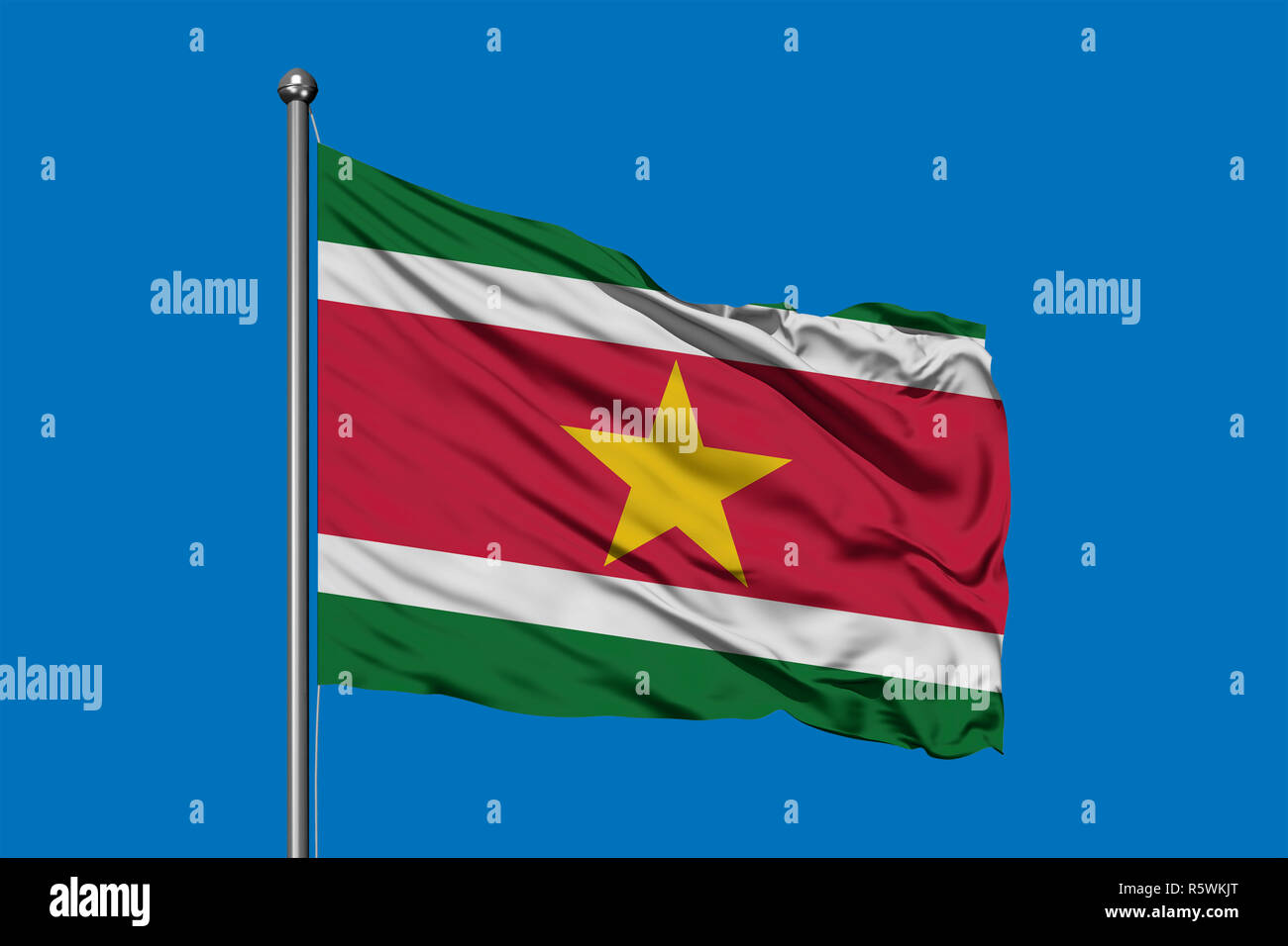 Flag of Suriname waving in the wind against deep blue sky. Surinamese flag. - Stock Image