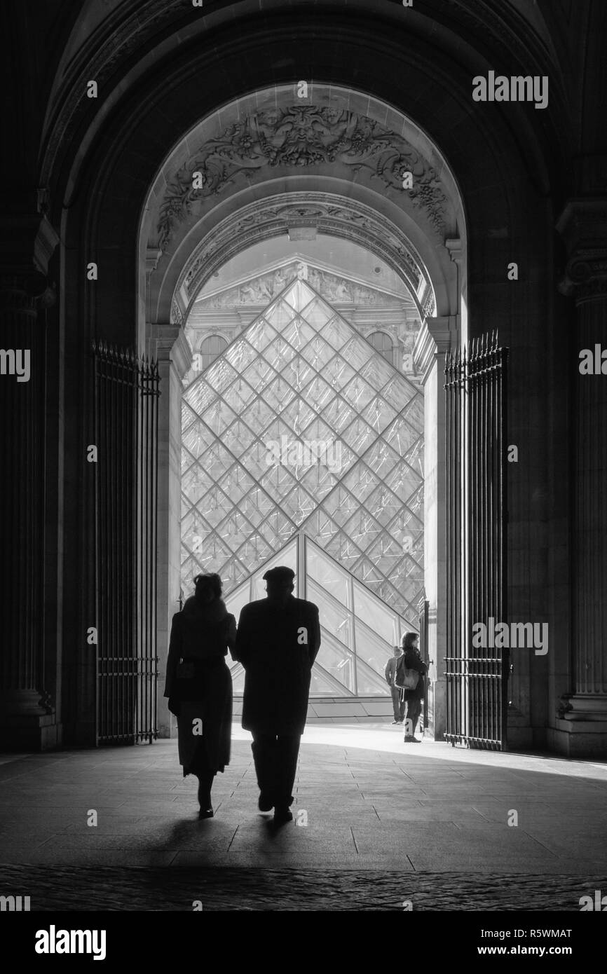 Romantic couple walking within the Louvre in Paris, France - Stock Image