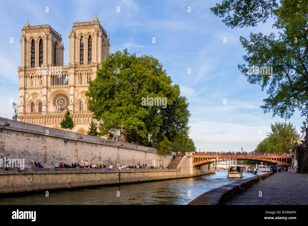 People relaxing on the Seine River with the Cathedral of Notre Dame in the background - Stock Image