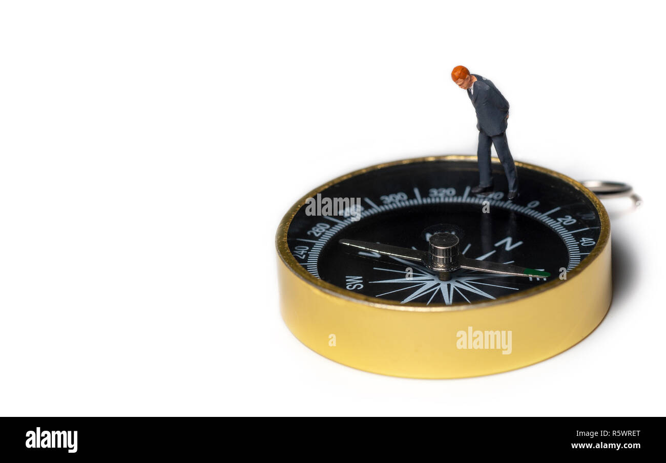 miniature figure businessman in dark blue suit standing on golden compass  for finding the way how to success of business and financial - Stock Image