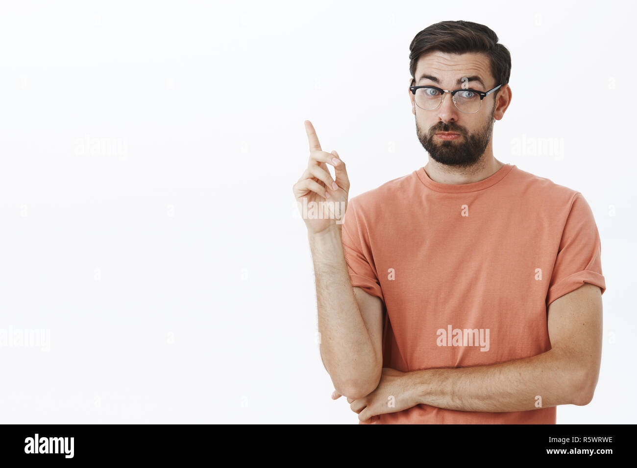 Cute teacher with beard in glasses raising index finger to make point, teach something and say smart things, standing wise and intelligent over gray b - Stock Image