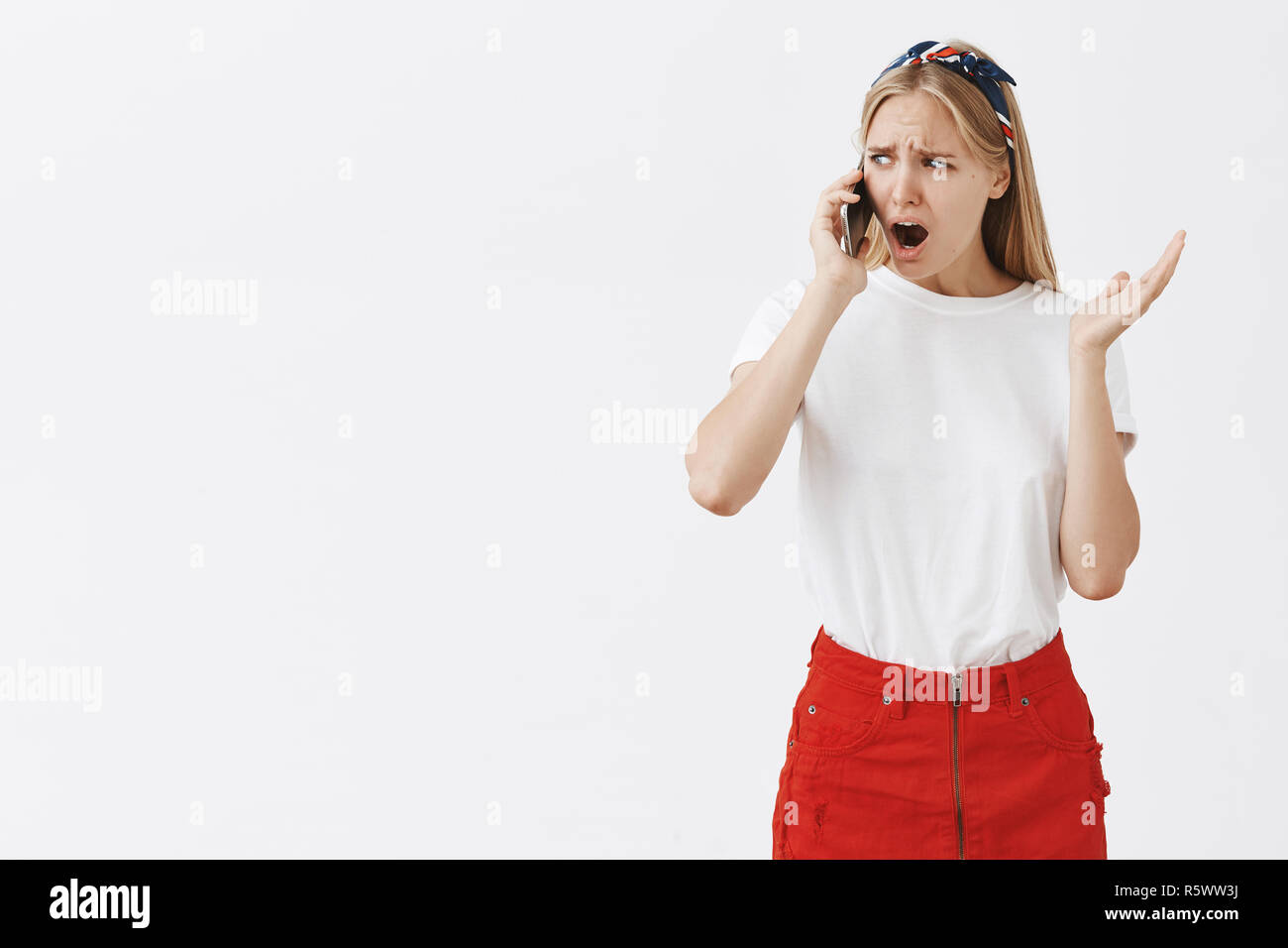 Studio shot of displeased moody girlfriend with blond hair frowning and compaining while talking on smartphone, gesturing and grimacing being displeas - Stock Image