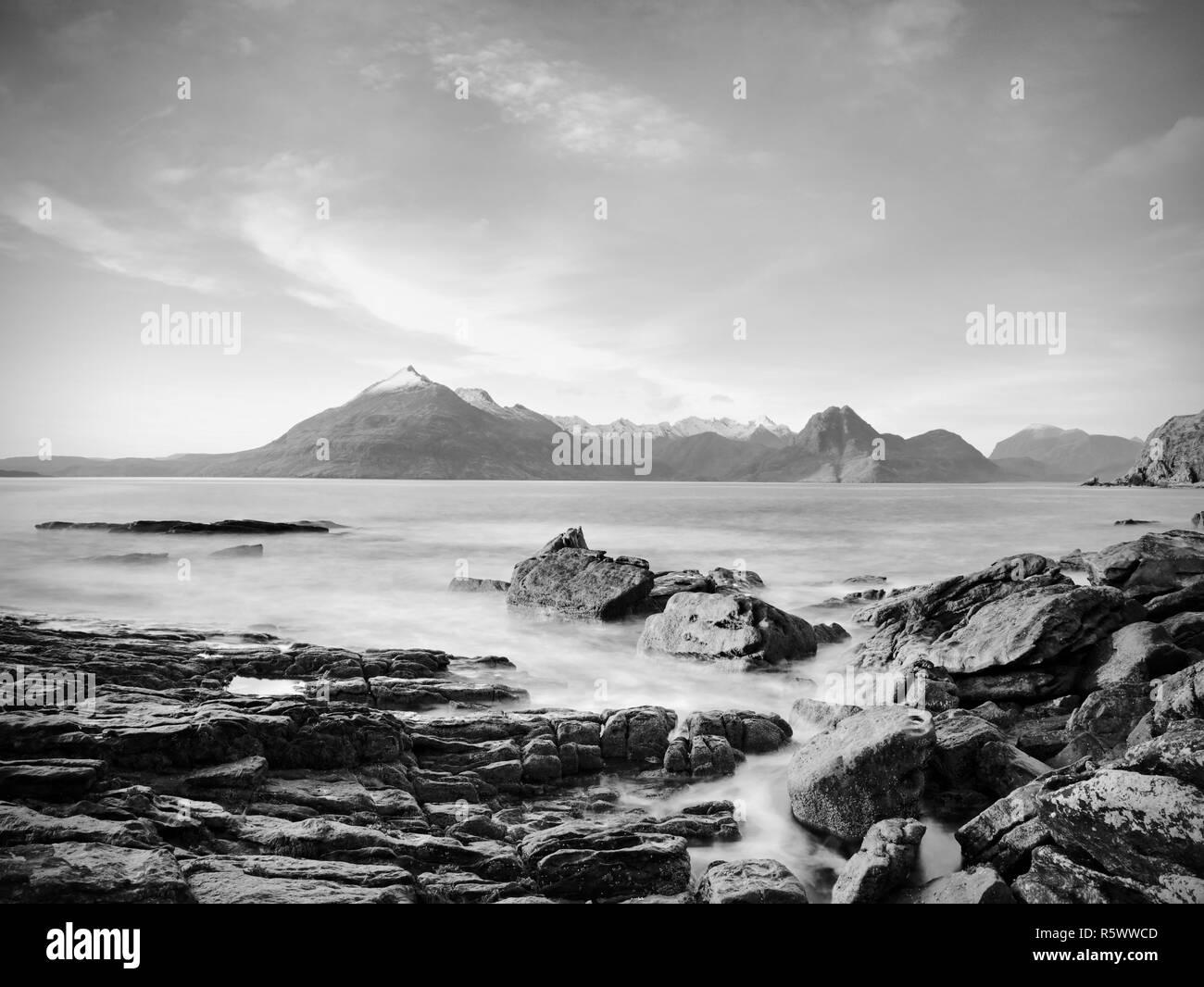 The stony beach and cliff of rocky bay. Blue tones of February sunset, pink horizon.  Dark slipery boulders with deep cracks. - Stock Image