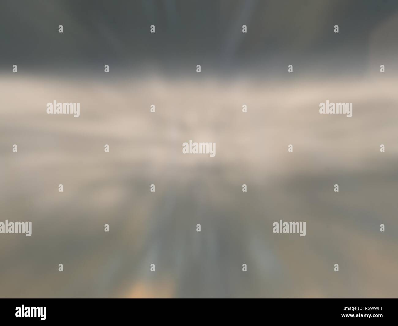 Blurry lake background. Foggy morning lake in the forest with calm water on the lake and the reflection of the sky - Stock Image