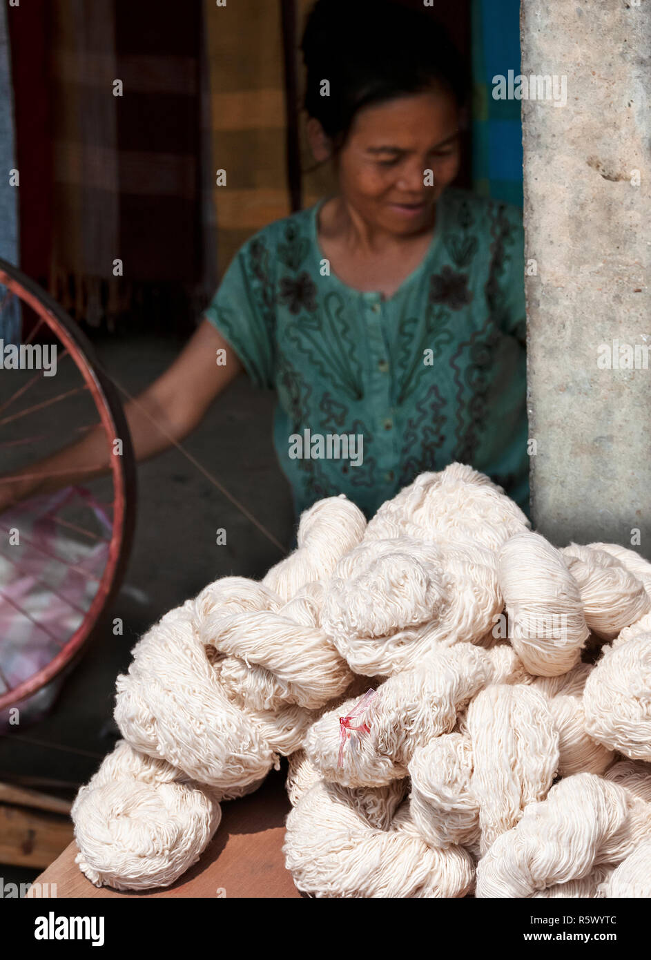 Laotian woman spinning wool into yarn which she's wrapped into loose twists called skeins which are ready to knit from near Luang Prabang, Laos, Lao - Stock Image