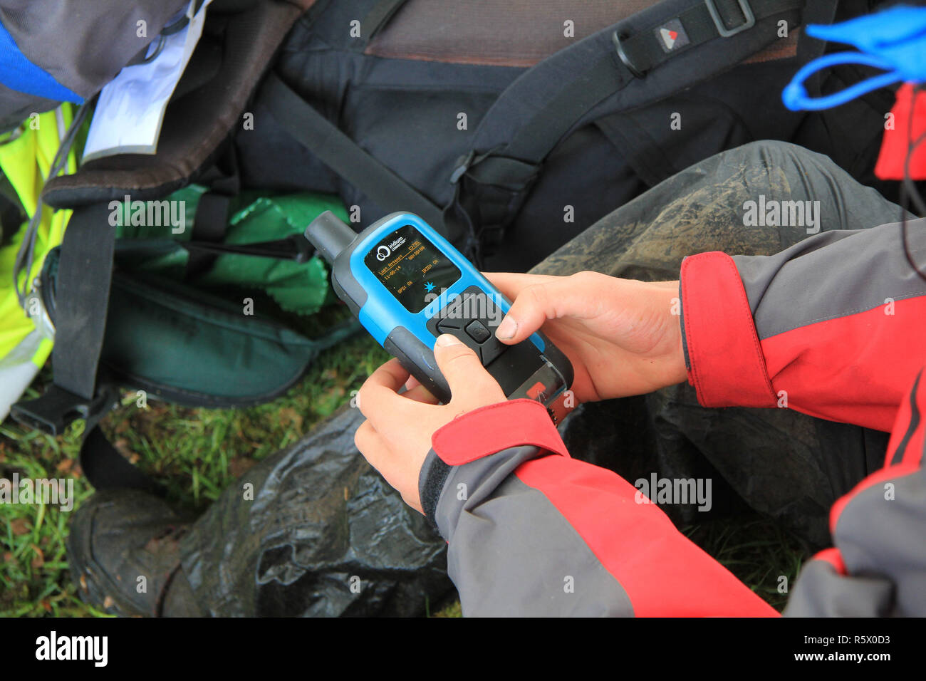 Participant checks his Iridium tracker at a checkpoint during the Ten Tors event on Dartmoor Stock Photo