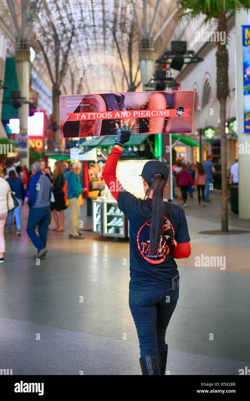 Young woman twirling a placard advertising tattoos in the Freement Street area of old downtown Las Vegas, Nevada - Stock Image