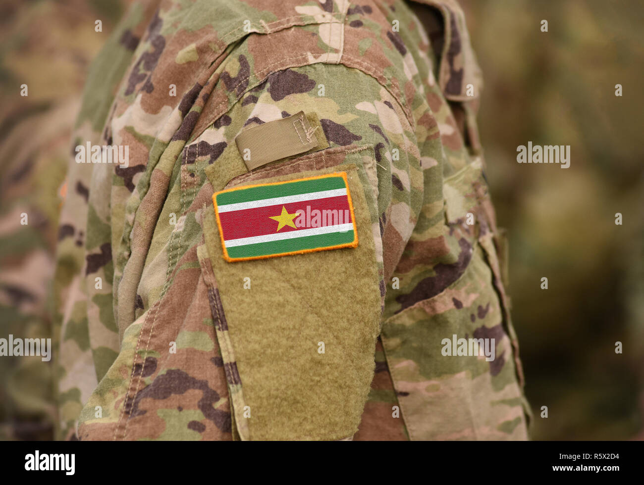 Flag of Suriname on soldiers arm (collage). - Stock Image