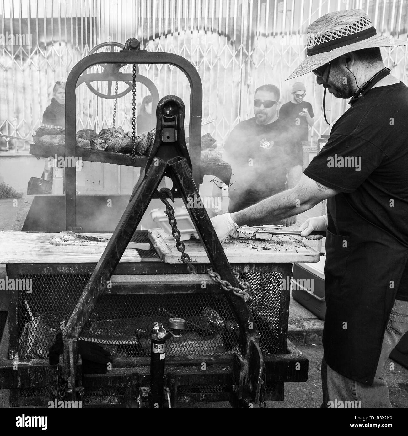 OAKLAND, CA-June 6, 2014: Street chef at Art Murmur cooks bbq on an industrial strength grill. Gritty urban setting. Black and white square format. - Stock Image