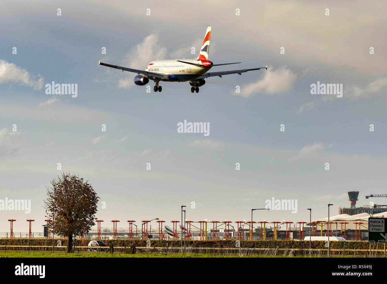 LONDON, ENGLAND - NOVEMBER 2018: Passenger jet passing over the Instrument Landing System antennae of a runway at London Heathrow Airport - Stock Image