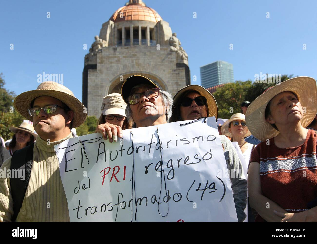 Mexico City, Mexico. 02nd Dec, 2018. A woman holds a sign that reads 'PRI's authoritarianism returns transformed' during a protest against Mexican President, Andres Manuel Lopez Obrador, in Mexico City, Mexico, 02 December 2018. Around two thousand people protested against the new president on the first day of his term after his investiture yesterday. Credit: Mario Guzman/EFE/Alamy Live News Stock Photo