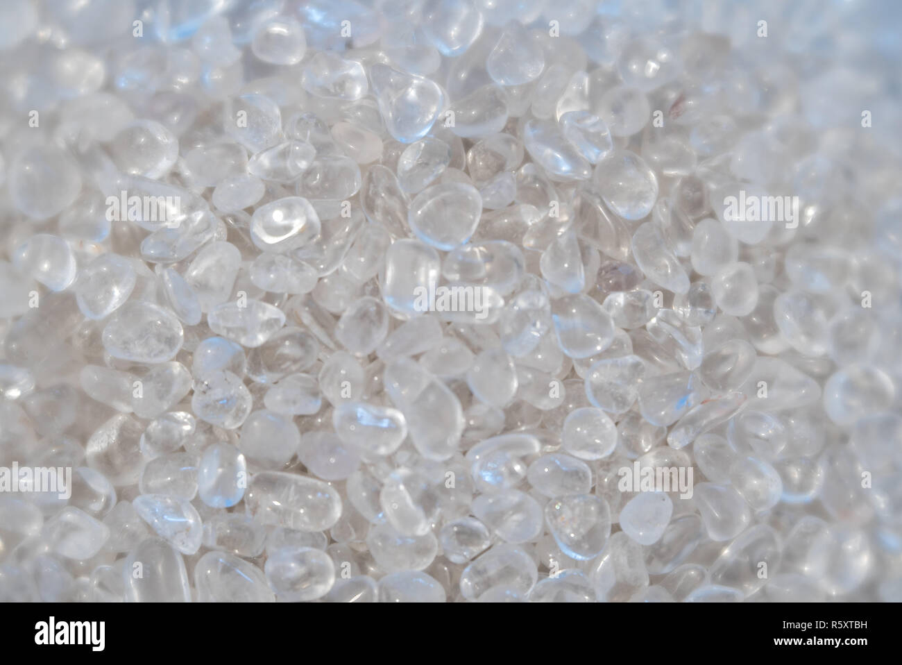 horizontal background of small polished quartz and rock crystal stones in a giant pile Stock Photo