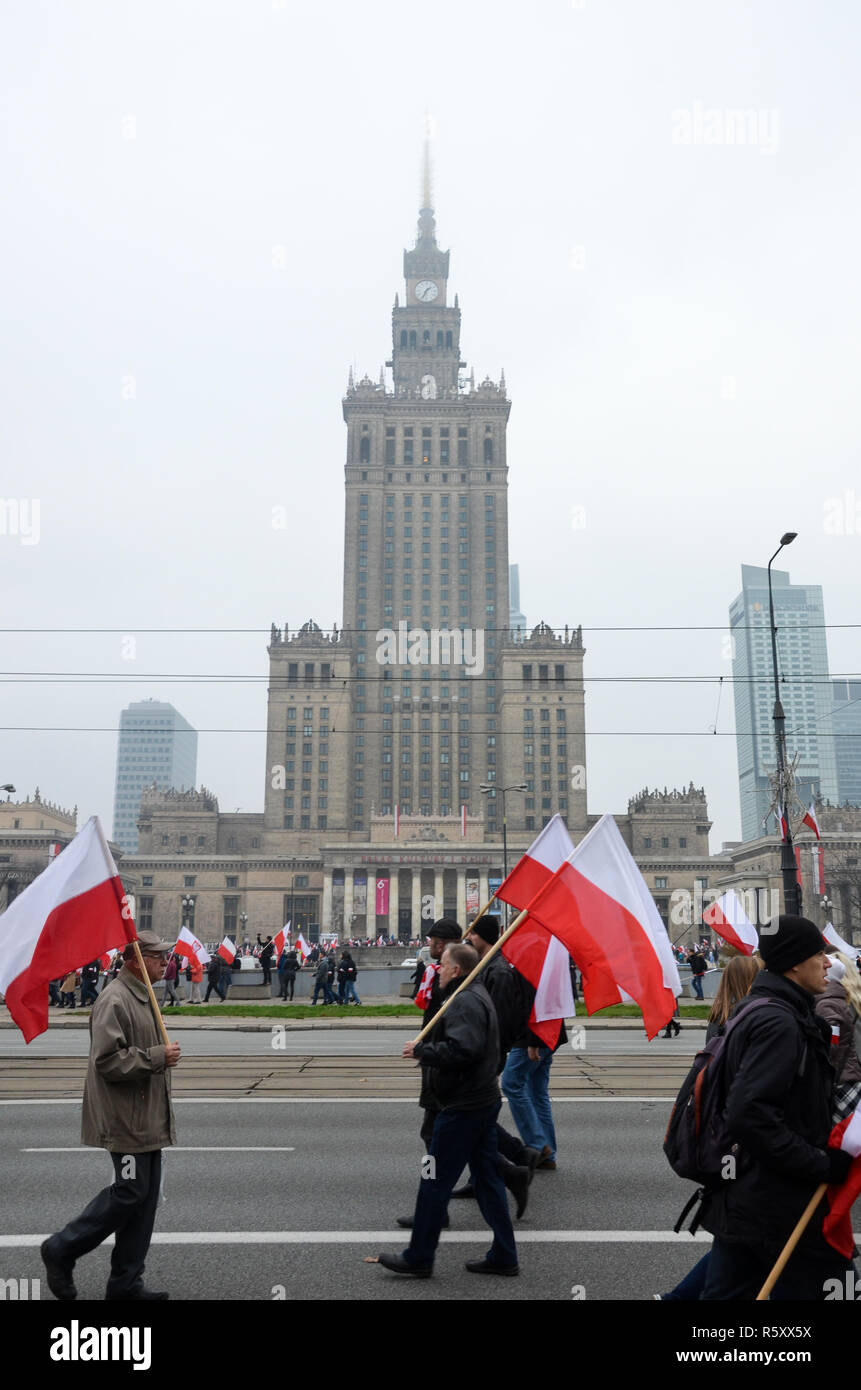 People carry Polish flags past the Palace of Culture, National Independence Day march, 100 year anniversary, Warsaw, 11 November, Poland, 2018 - Stock Image
