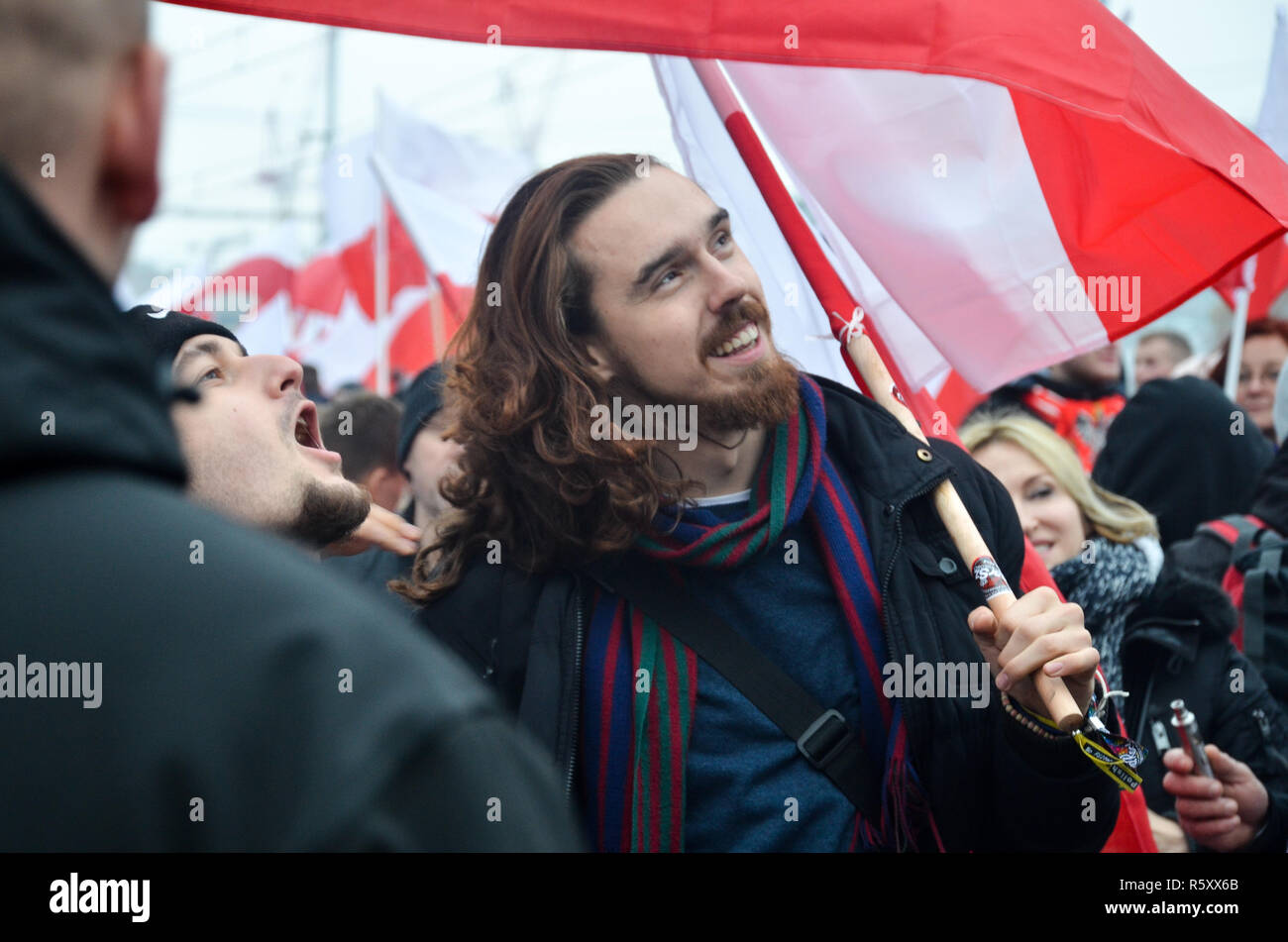 A man holds the Polish flag and smiles, Polish National Independence Day march, 100 year anniversary, Warsaw, 11 November, Poland, 2018 - Stock Image