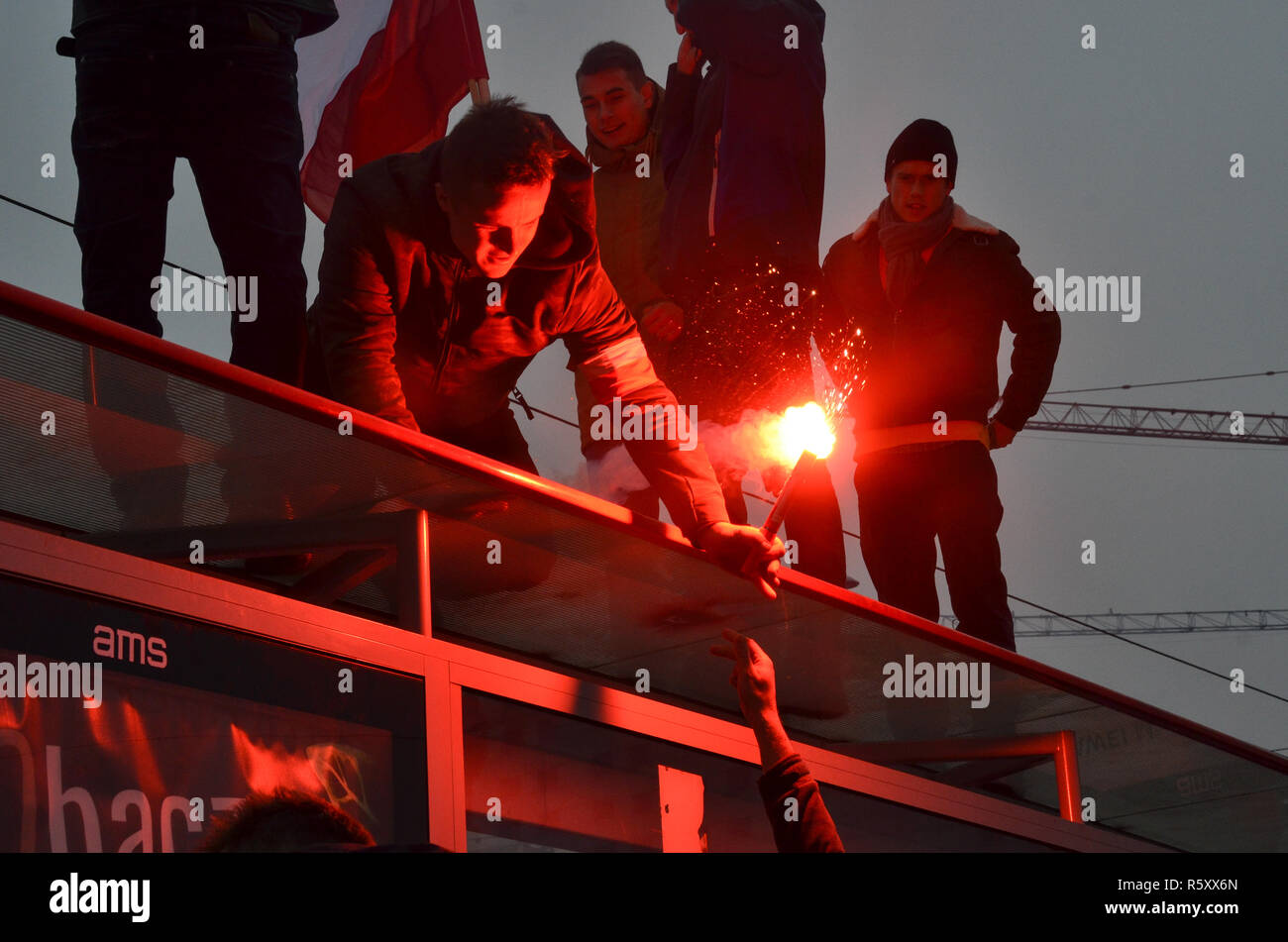 A man hands over a flare on top of a bus stop, Polish National Independence Day march, 100 year anniversary, Warsaw, 11 November 2018, Poland, 2018 Stock Photo