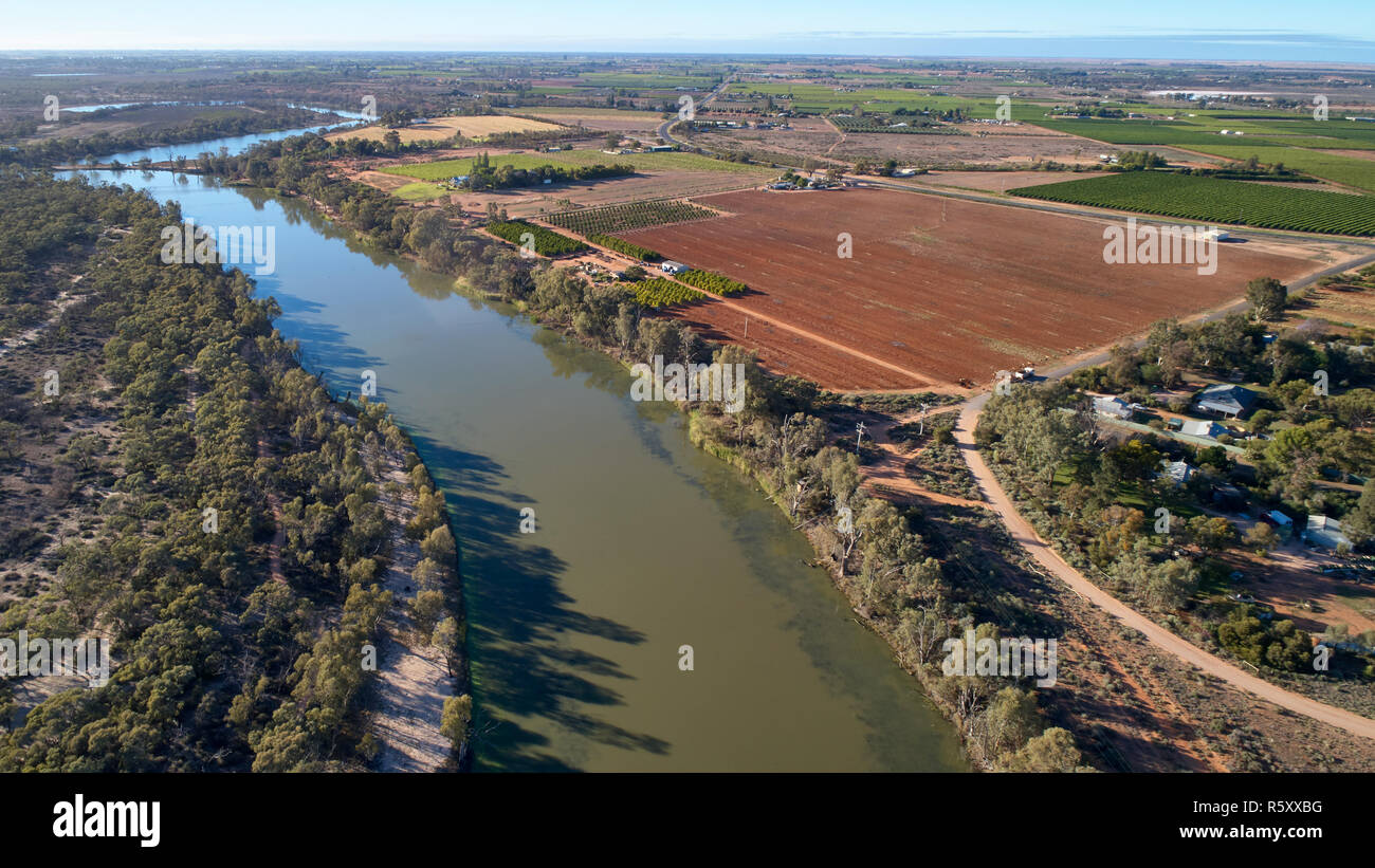 Low altitude aerial of Cowanna Billabong with irrigated farmland and vineyards in the background. - Stock Image