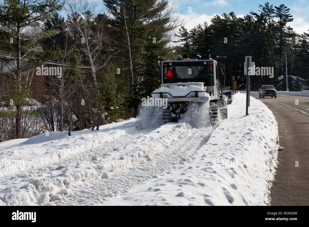 A Prinoth  Husky snow groomer driving down the sidewalk, part of a snowmobile trail, in Speculator, NY USA in the Adirondacks Park. - Stock Image
