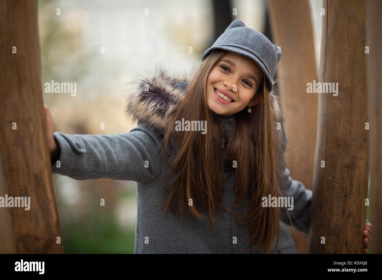 Photo of girl in gray hat and coat among trees on blurred background - Stock Image