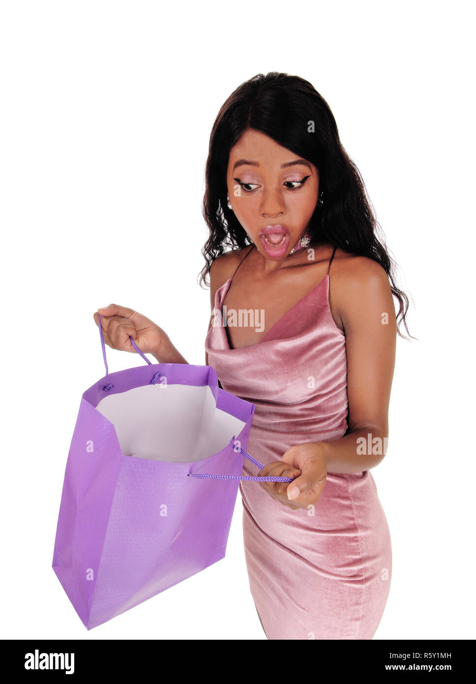 Woman looking surprised in her shopping bag - Stock Image