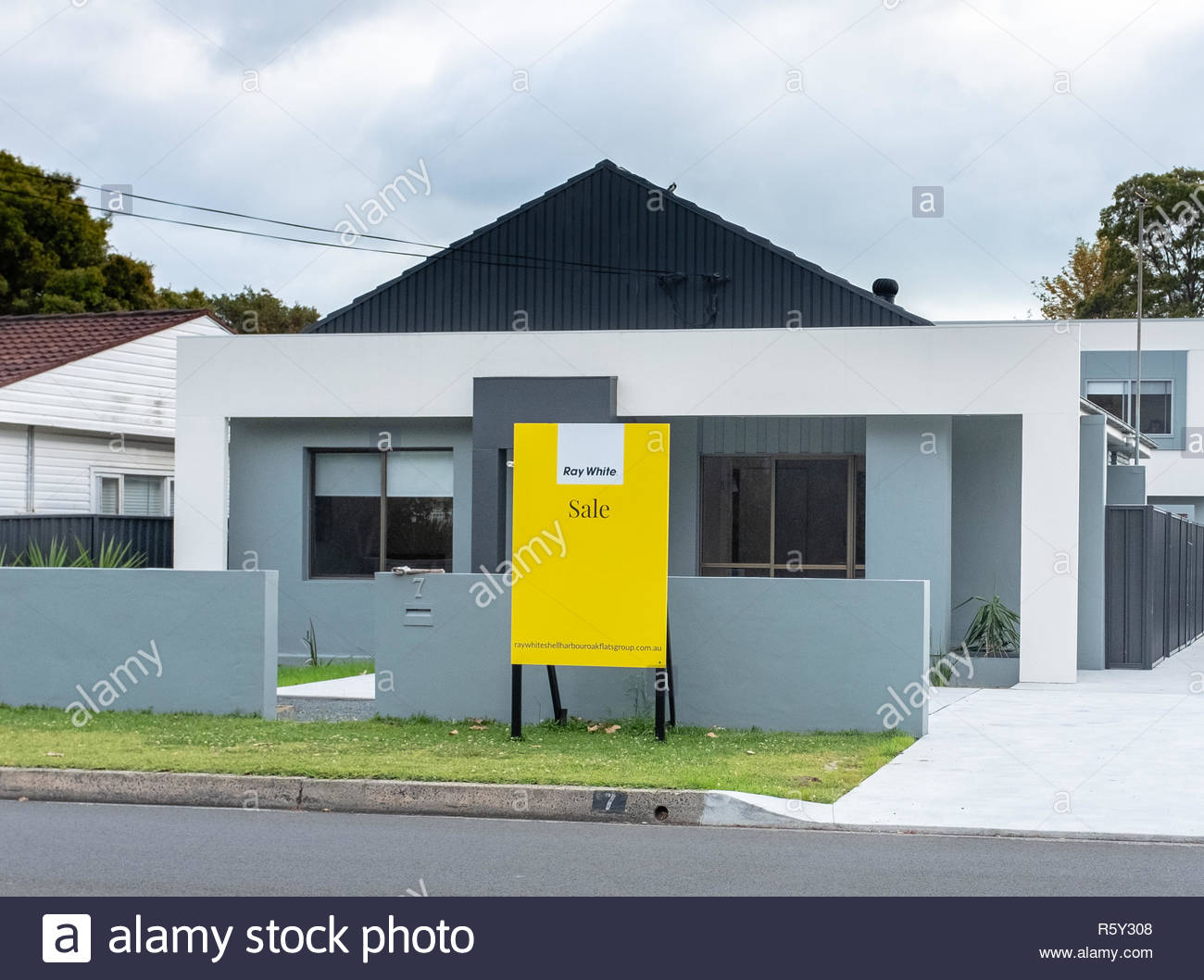 Australian For Sale signs Ray White estate agent, outside new build house, NSW, Australia - Stock Image
