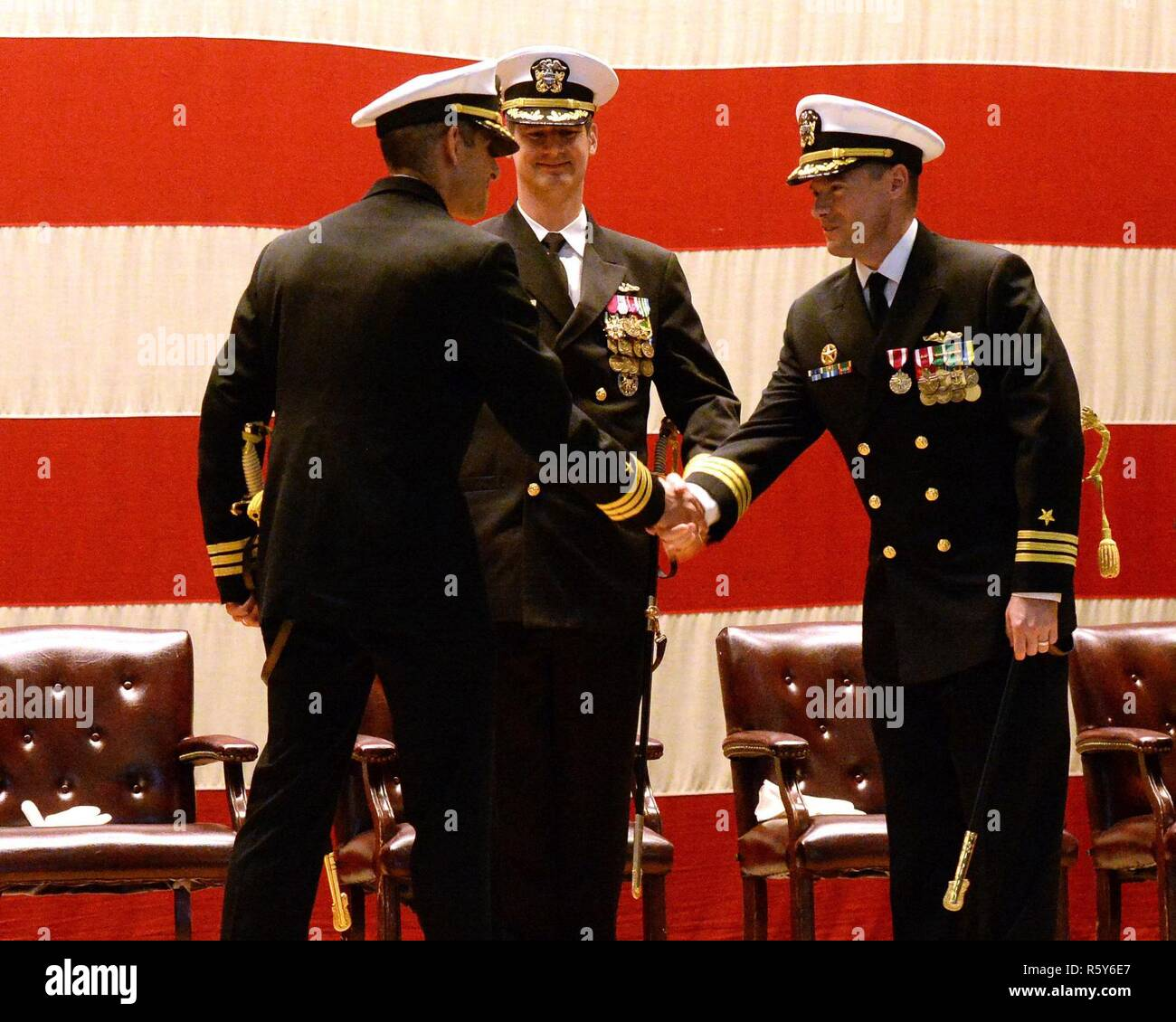 GROTON, Conn. (April 21, 2017) (Left) Virginia Class, fast-attack, submarine, USS San Juan (SSN 751)'s new Commanding Officer, Cmdr. Ravi Desai shakes hands with San Juan's former Commanding Officer, Cmdr. John Craddock after relieving him of command in the presence of Commander, Submarine Squadron Twelve Commodore, Capt. Ollie Lewis. Desai and Craddock exchanged command during a ceremony held in the Dealey Theater aboard Naval Submarine Base New London on April 21, 2017. - Stock Image